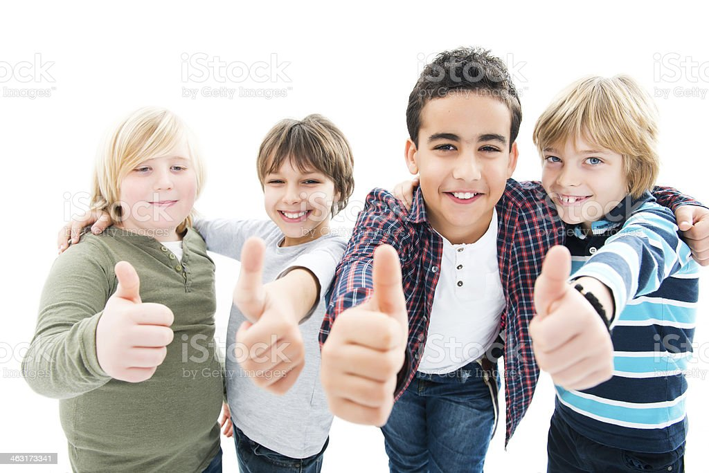 Smiling embraced boys with thumbs up over white background stock photo