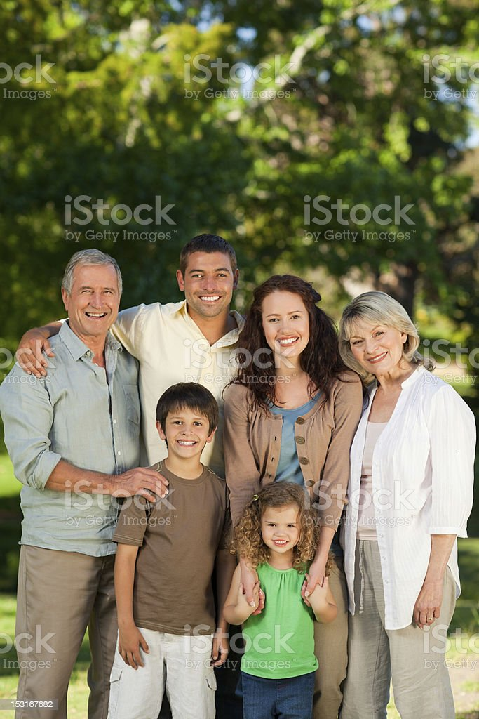 Smiling embracing family portrait outside in a park royalty-free stock photo