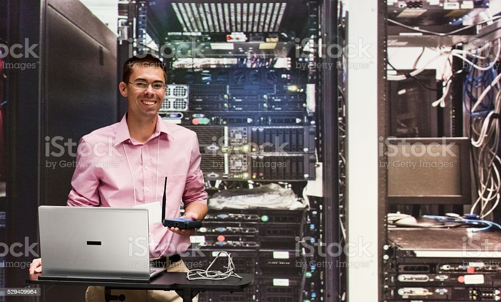Smiling engineer working with laptop stock photo