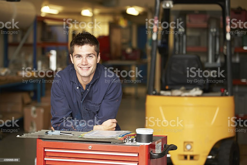 Smiling engineering apprentice in factory stock photo