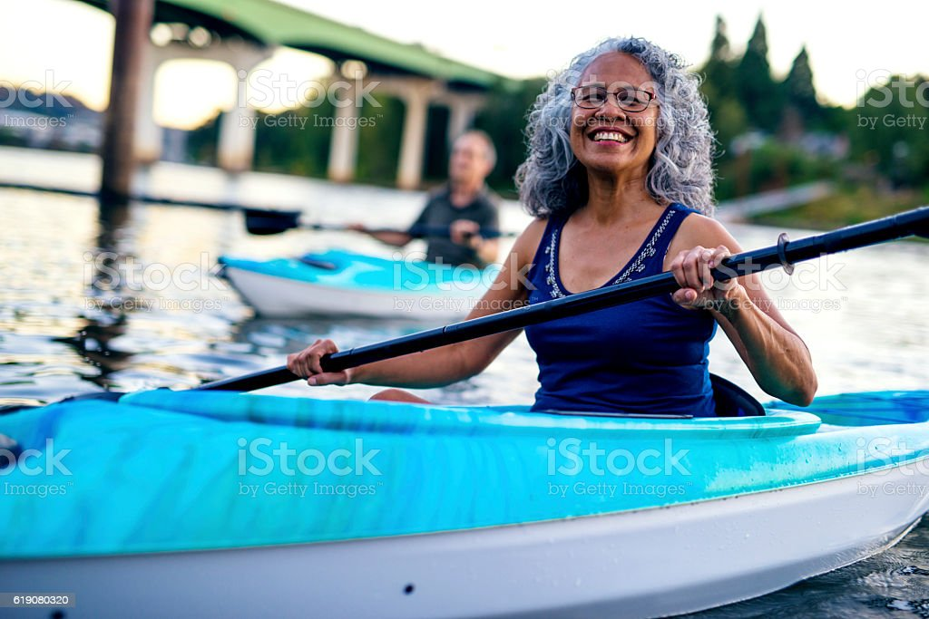 Smiling ethnic elderly woman kayaking with her husband stock photo
