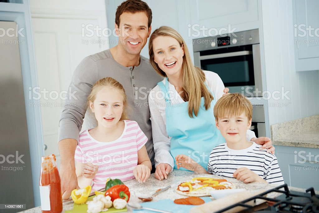 Smiling family cooking pizza royalty-free stock photo