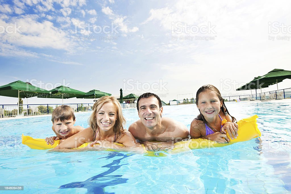 Smiling family enjoying in the pool. royalty-free stock photo