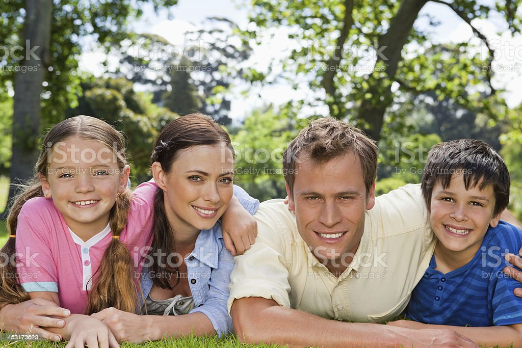 Smiling family looking at the camera while lying on lawn royalty-free stock photo