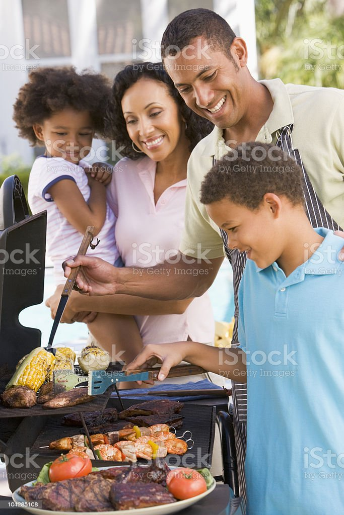 A smiling family of 4 is barbecuing outside their home royalty-free stock photo