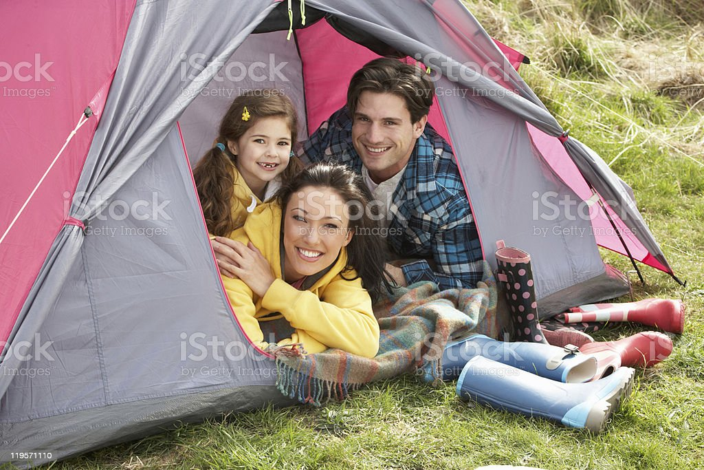 Smiling family of three in a tent camping in the woods royalty-free stock photo