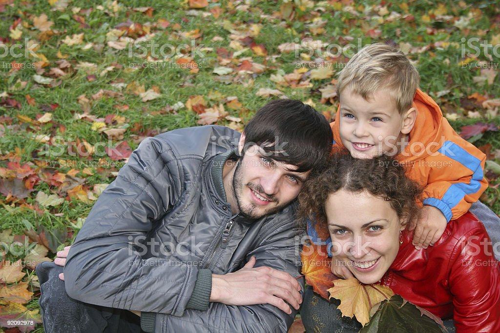Smiling family of three sitting outdoors by fallen leaves royalty-free stock photo