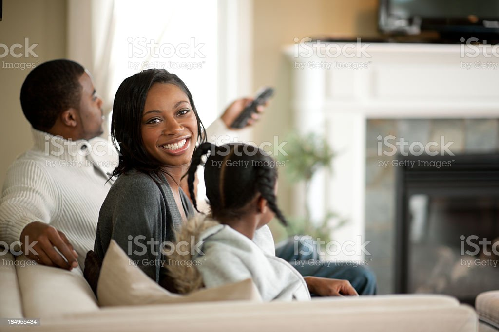 Smiling family on couch watching television stock photo