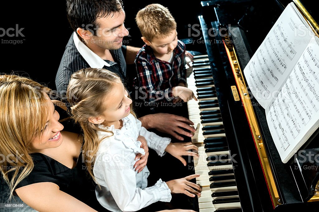 Smiling family playing piano together. stock photo