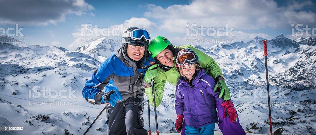 Smiling family portrait on ski slope stock photo