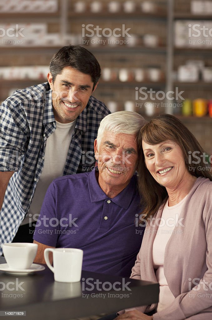 Smiling family sitting in cafe stock photo