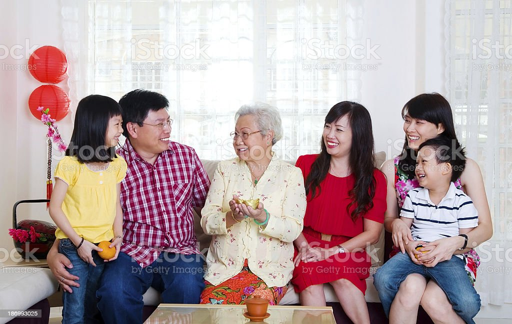 Smiling family sitting on couch celebrating Chinese New Year stock photo