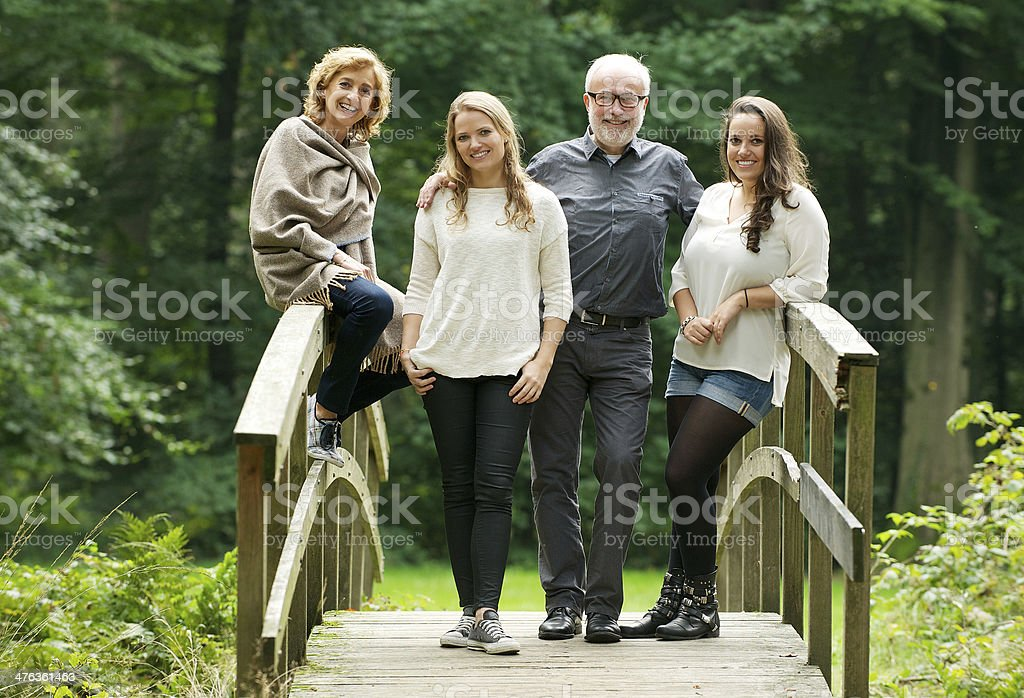 Smiling family standing on bridge in the forest stock photo