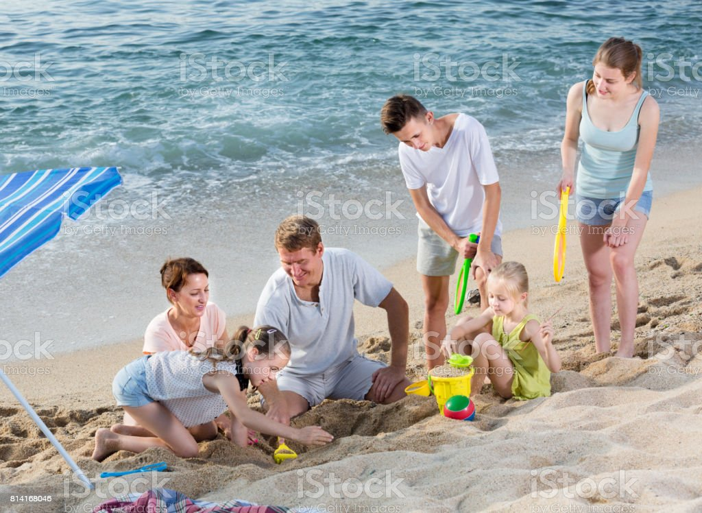 Smiling family with four children playing on sea beach stock photo