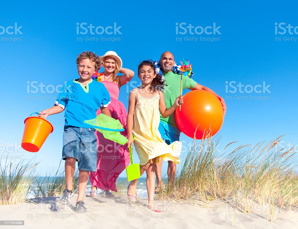 Smiling family with orange beach ball standing on beach dune royalty-free stock photo