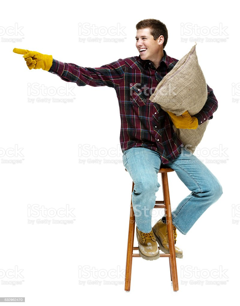 Smiling farmer holding burlap sack and pointing stock photo