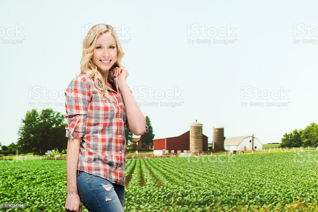 Smiling farmer in front of farm stock photo