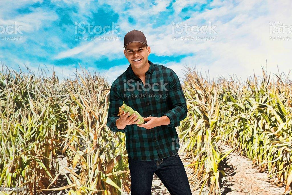 Smiling farmer standing in corn farm stock photo
