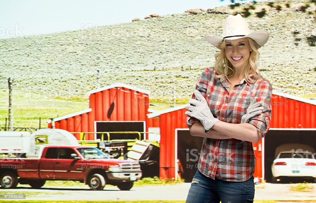 Smiling farmer standing in front of farmhouse stock photo