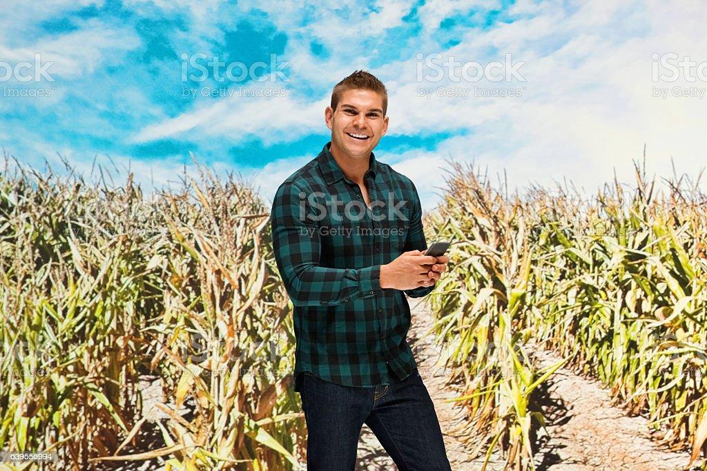 Smiling farmer using phone in farm stock photo
