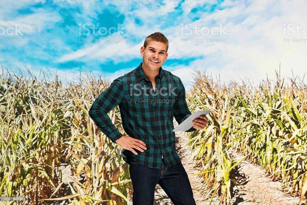 Smiling farmer using tablet in corn field stock photo