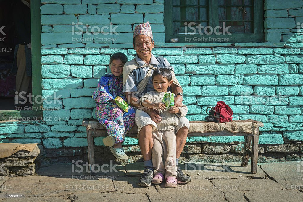 Smiling farming family sitting in sunshine high in Himalayas Nepal stock photo