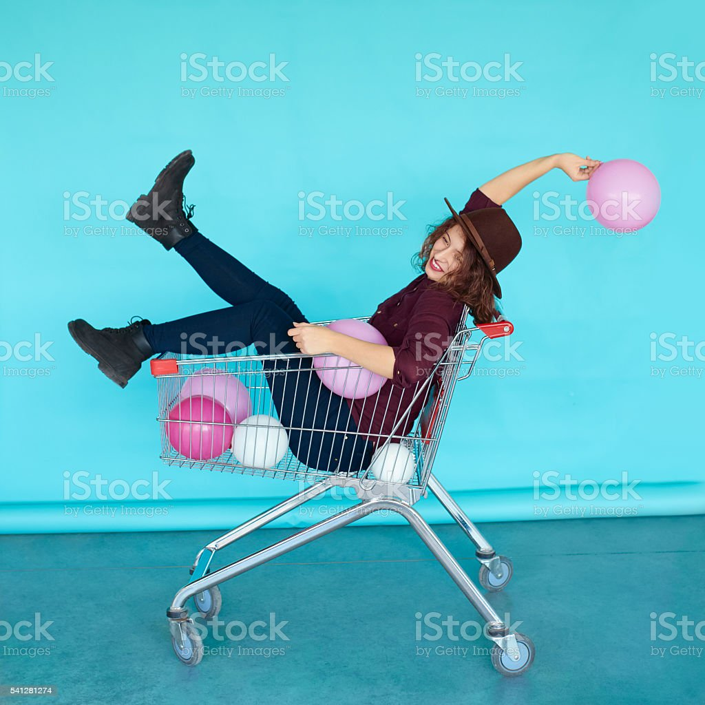smiling fashion brunette girl sitting in shopping cart stock photo