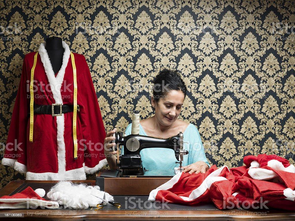 Smiling fashion designer sewing santa costume for christmas stock photo