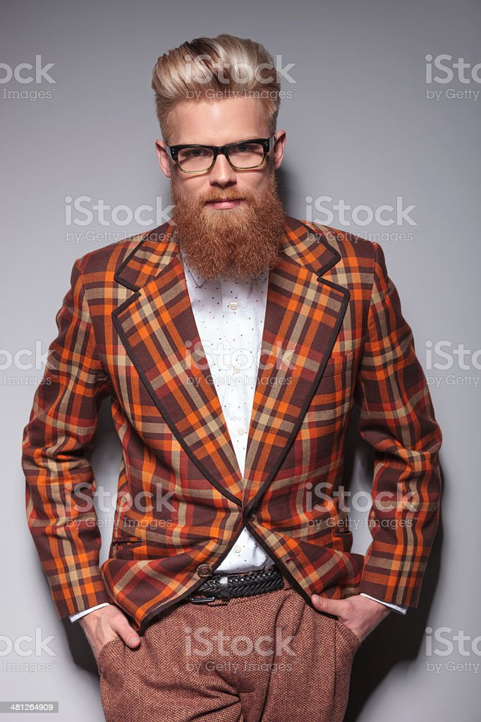 smiling fashion model with long beard leaning against gray wall stock photo