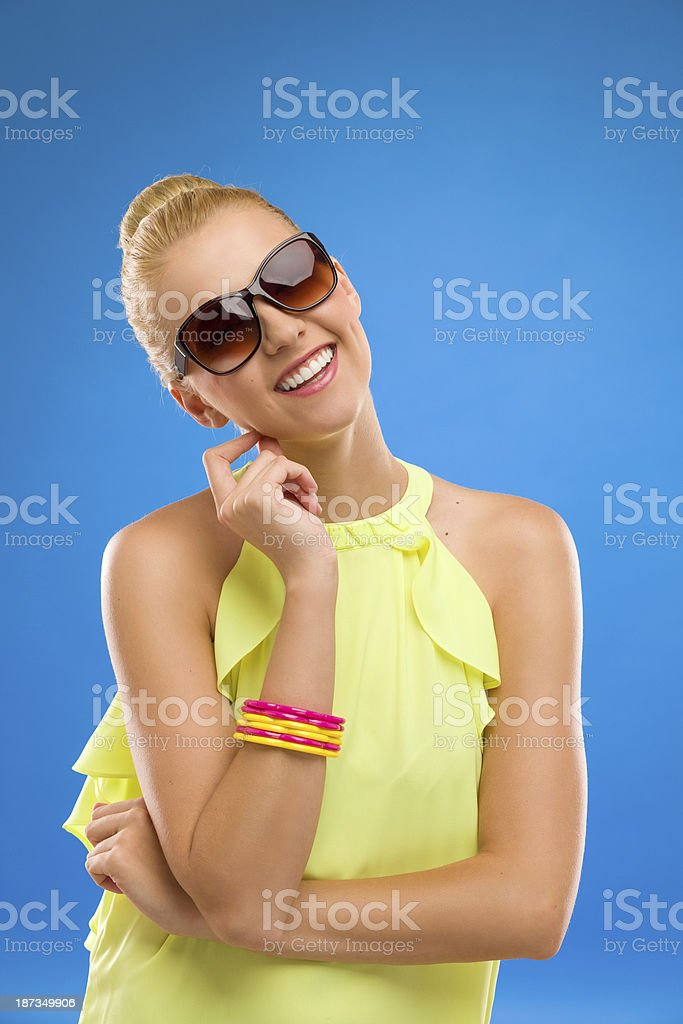 Smiling fashion woman in sunglasses on blue background. royalty-free stock photo