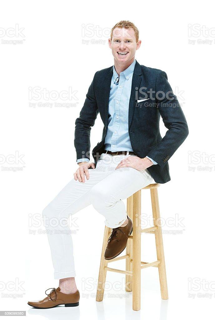 Smiling fashionable man sitting on stool stock photo