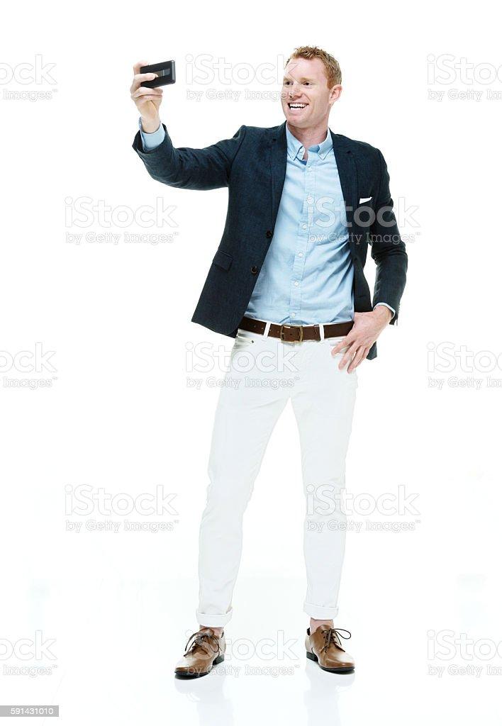 Smiling fashionable man taking a selfie stock photo