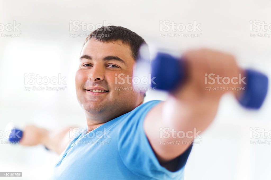 Smiling fat man weightlifting and looking at camera. stock photo