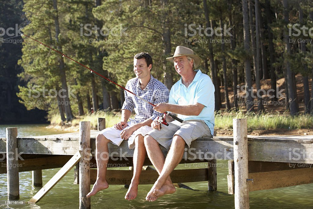 Smiling father and adult son sitting on a dock, fishing stock photo
