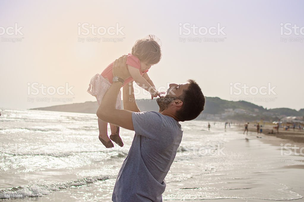 Smiling father and daughter at the beach stock photo