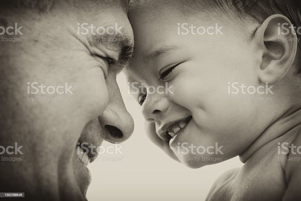 Smiling father and smiling toddler looking at each other stock photo