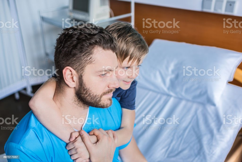 Smiling father and son hugging while sitting on hospital bed, dad and son in hospital stock photo