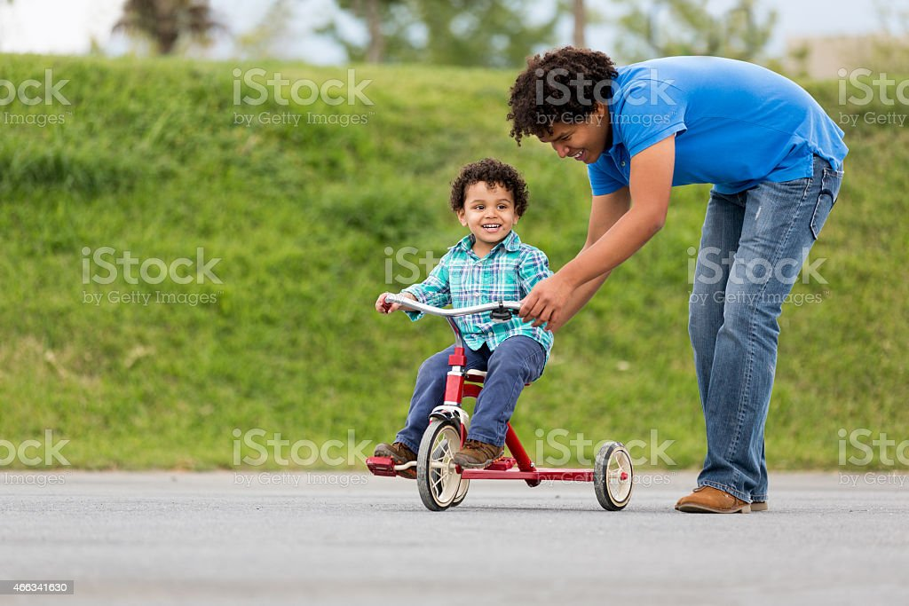Smiling father assisting son in tricycle stock photo
