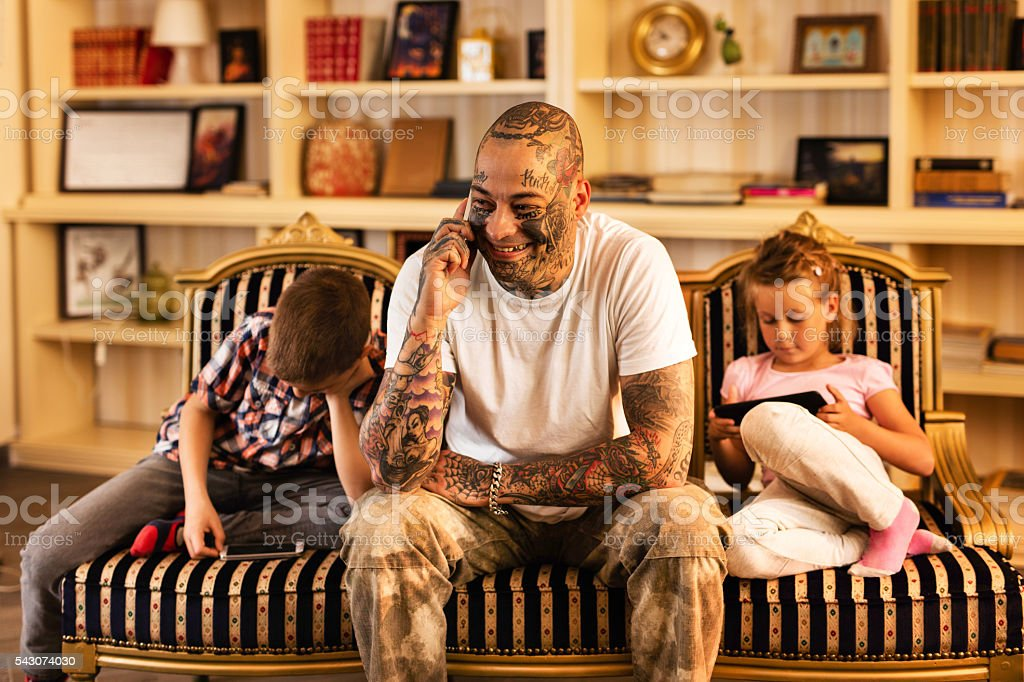 Smiling father communicating over cell phone at home. stock photo