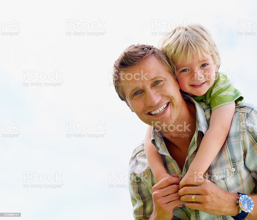 Smiling father giving his son piggyback ride against white royalty-free stock photo