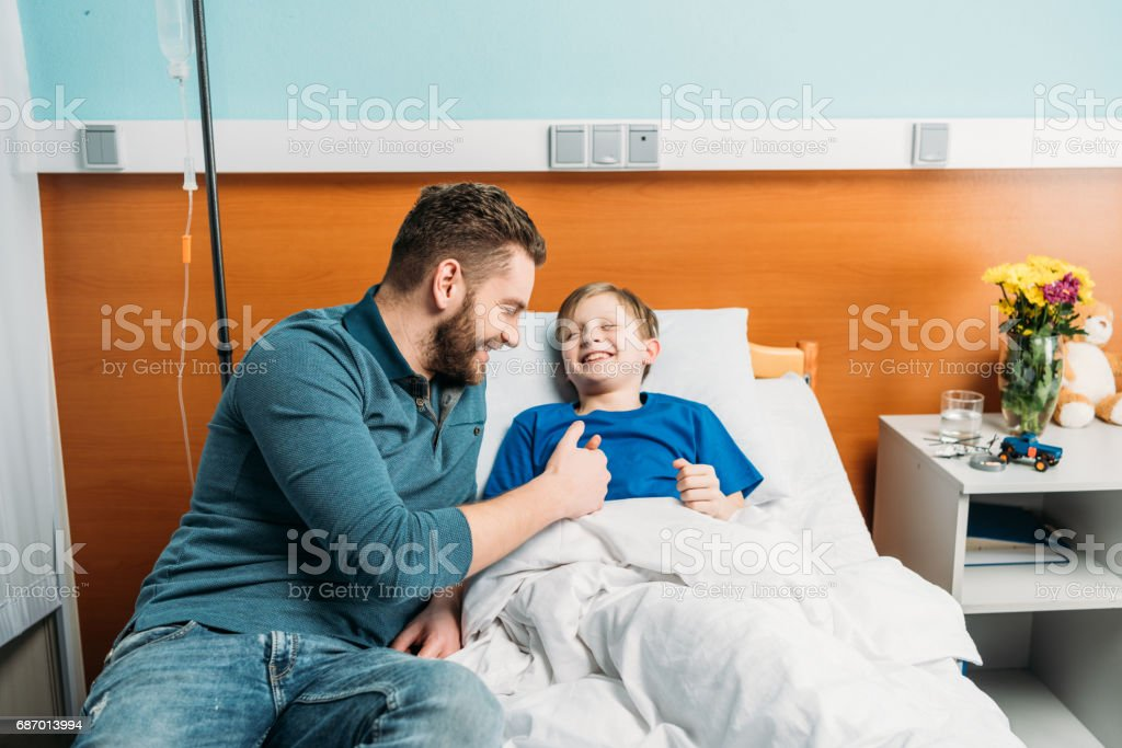 Smiling father playing with cute little son lying in hospital bed, dad and son in hospital stock photo