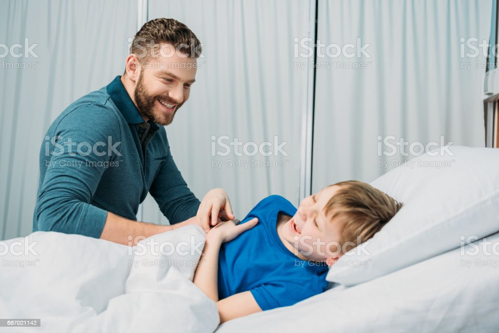 Smiling father playing with sick little boy lying in hospital bed, dad and son in hospital stock photo