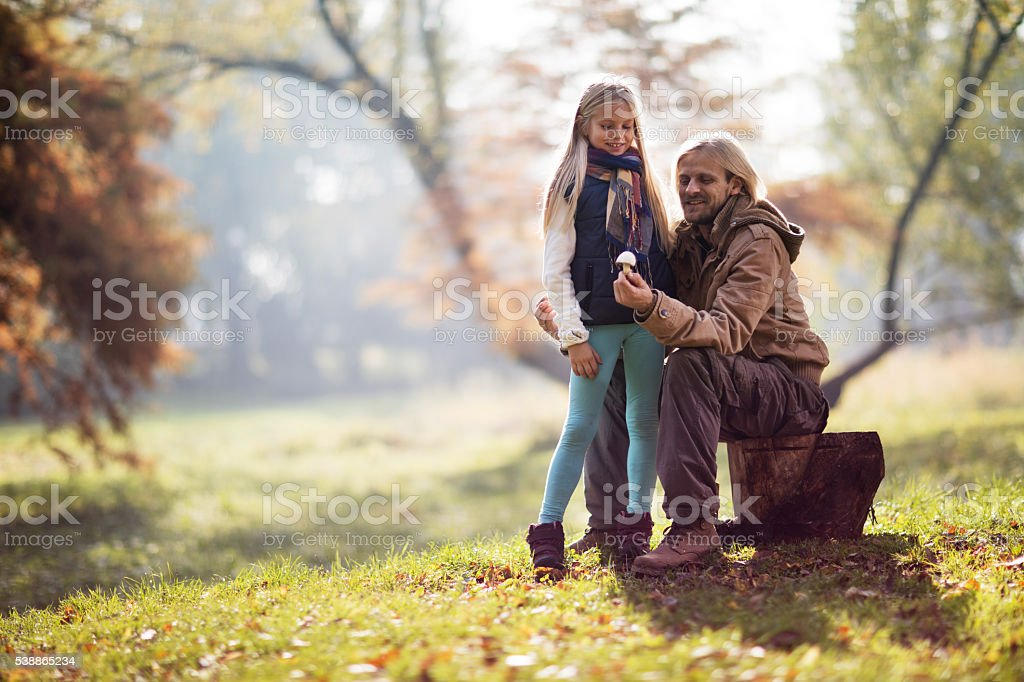 Smiling father showing a mushroom to his daughter in nature. stock photo