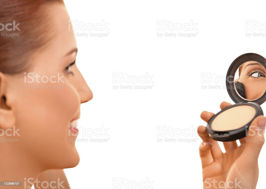 Smiling female applying make-up royalty-free stock photo