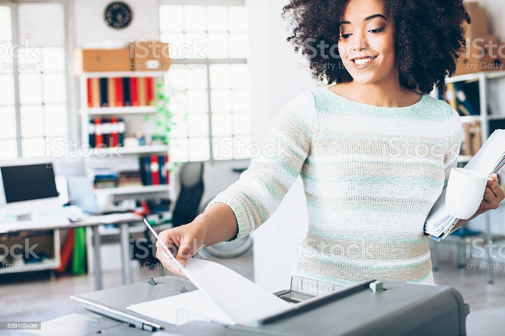 Smiling female assistant using copy machine at work stock photo