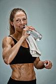 Smiling female athlete drinking water