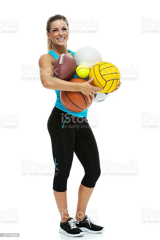 Smiling female athlete holding sports ball stock photo