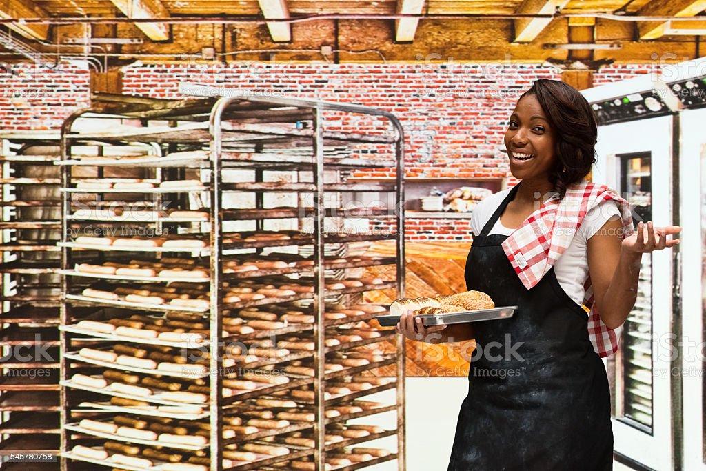 Smiling female baker presenting in bakery stock photo