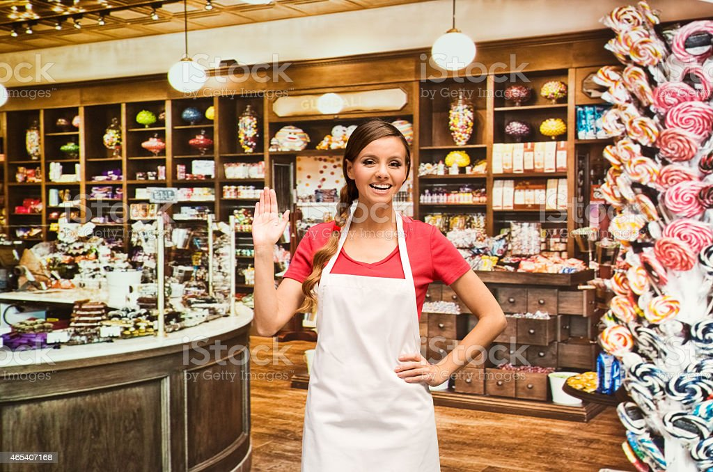 Smiling female baker waving hand in candy store stock photo