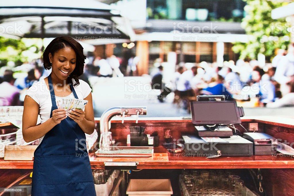 Smiling female bartender holding money outdoors stock photo